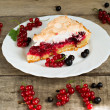 Piece of berry pie, red and black currants on white plate and wooden table — Stock Photo
