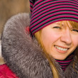 Stock Photo: Portrait of smiling girl in knitted cap in wintry park