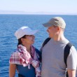 Portrait of happy young couple outside on coast over blue sea — Stock Photo