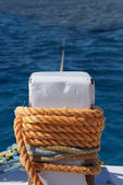 Close-up of mooring bollard with orange rope — Stock Photo