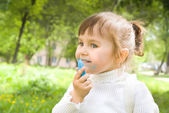 Cute little hellion girl with blue chalk — Stock Photo