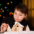 Young woman decorating gingerbread house — Stock Photo #42667261