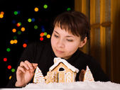 Young woman decorating gingerbread house — Stock Photo