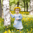 Pretty toddler girl with floral head wreath on the meadow with yellow flowers — Stock Photo #46899885