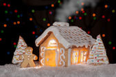 Gingerbread house with gingerbread man and christmas trees — Stock Photo