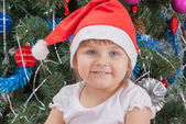 Portrait of happy cute little girl in red Santa hat — Stock Photo