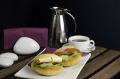 Two sandwich on white china plate, cup of tea and thermos on table — Stock Photo