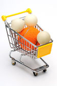 Shopping cart, pingpong ball and tennis ball — Stock Photo