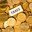Taxes sign on golden coins — Stock Photo