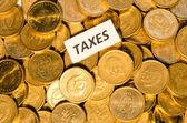 Taxes sign on golden coins — Photo