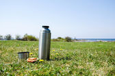 Thermos on grass field — Stock Photo