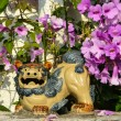 Shisa figure and pink flowers — Stock Photo #37664885
