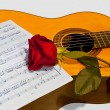 Stock Photo: Guitar and rose on light background.