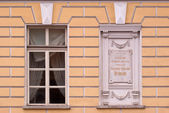 A window with a memorial plate. — Stock Photo