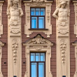 The facade of the building with antique sculptures. — Stock Photo