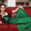 Beautiful smart girl with clean skin and makeup in the current trend, lying on the sofa in a red vest and a long green dress with a jeweled necklace and a black bag. Fashion and Beauty. Portrait of a — Stock Photo