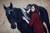 Lovely and beautiful girl of the European appearance brunette with brown horse in winter nature with accessories. Fashion and beauty. Animal and natural. — Stock Photo