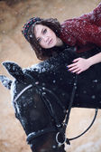 Lovely and beautiful girl of the European appearance brunette with brown horse in winter nature with accessories. Fashion and beauty. Animal and natural. — Foto Stock