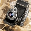 Old camera on photos — Stock Photo