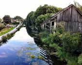 Leeds canal , Armley, early autumn day, clouds and sky reflecting off the water surface, next to an abandoned derelict old warehouse — Stock Photo