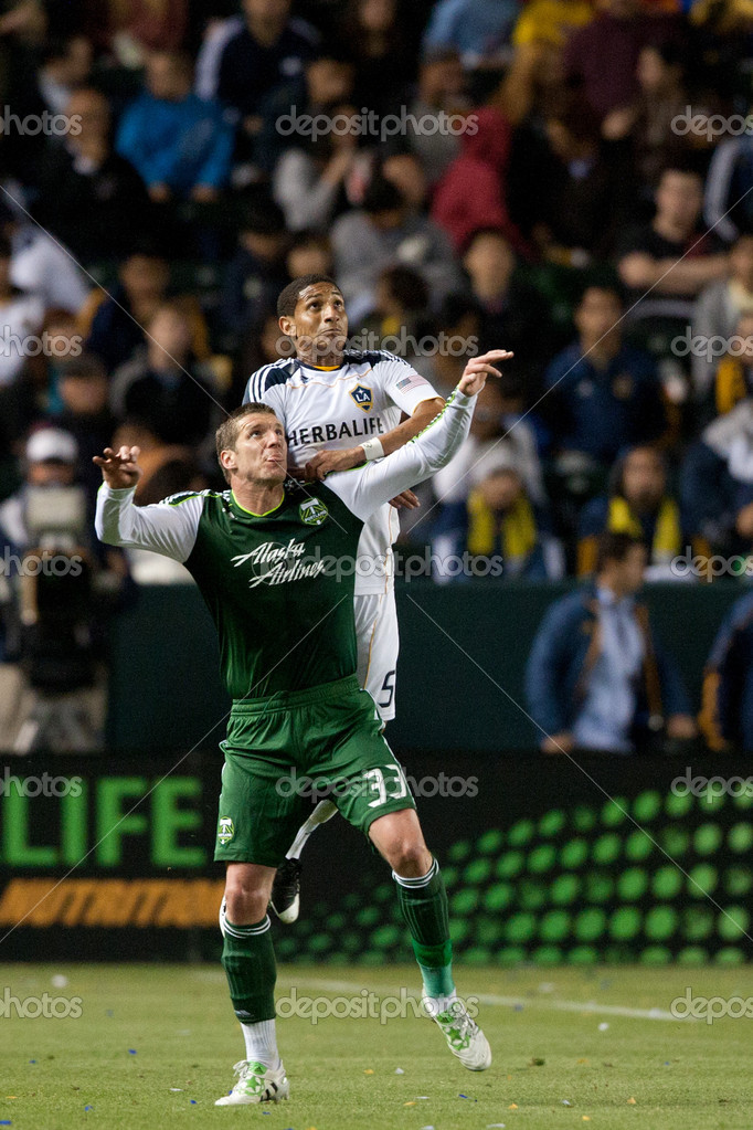 CARSON, CA. - April 23. Los Angeles Galaxy defender Sean Franklin N5 gets over Portland Timbers forward Kenny Cooper N33 in anticipation of header during the Major L — Foto de Stock   #14180164