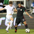 Постер, плакат: Michael McGlinchey and Giovani Dos Santos fight for the ball during the match