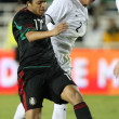 Постер, плакат: Giovani Dos Santos and Ben SIgmund battle for the ball during the match