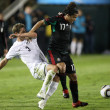 Giovani Dos Santos holds off Tony Lochhead to maintain possession of the ball during the match - Foto de Stock