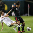 Foto de Stock  : Giovani Dos Santos holds off Tony Lochhead to maintain possession of ball during match