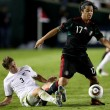 Giovani Dos Santos holds off Tony Lochhead to maintain possession of the ball during the match - Stock Photo