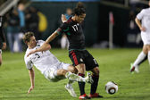 Giovani Dos Santos holds off Tony Lochhead to maintain possession of the ball during the match — ストック写真