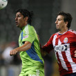 Постер, плакат: LEO GONZALEZ and ALAN GORDON fight for the ball during the game