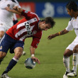 Постер, плакат: Alan Gordon gets away with a hand on the ball during the game