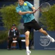 Tobias Kamke goes airborne in his return during the tennis game - Stock Photo