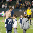 David Beckham and his kids walk off the pitch after the game - Stock Photo