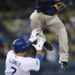 Stock Photo: MIGUEL TEJADjumps to avoid JAMES LONEY after he threw to first to complete double play during game