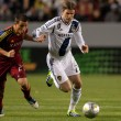 Постер, плакат: Luis Gil and David Beckham fight for the ball during the Major League Soccer game