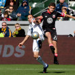 Landon Donovan and Chris Korb in action during the game - Stock Photo