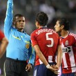 yader reyes gives marcelo saragosa a yellow card while mariano trujillo watches during the game — Stock Photo