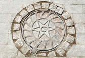 Manhole cover with the image of star — Stock Photo