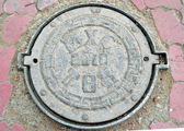 Manhole in Ulaanbaatar with Mongolian letters — Stock Photo