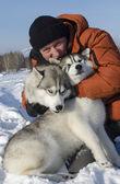 Mannen med två hundar av rasen husky på vintern i snön — Stockfoto