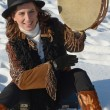 ストック写真: Nice girl in hat with tambourine in winter sitting on snow on city street in Irkutsk
