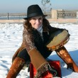 Nice girl in a hat with a tambourine in the winter on the city waterfront Irkutsk — Stock Photo