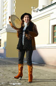 Nice girl in a hat with a tambourine in the winter on the city street in Irkutsk — Stock Photo