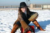 Leuk meisje in een hoed met een tamboerijn in de winter op de stad waterkant irkoetsk — Stockfoto