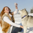 Young girl are playing with a dog of breed husky in the winter on the snow — Stock Photo