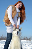 Young girl are standing with a dog of breed husky in the winter on the snow — Photo