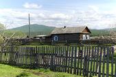 Casa de madeira sem pintura e uma cerca. aldeia de buryat. — Fotografia Stock
