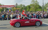 The parade on the streets of Irkutsk in honor of the City Day. Red taxi car. Side view. — Stock Photo